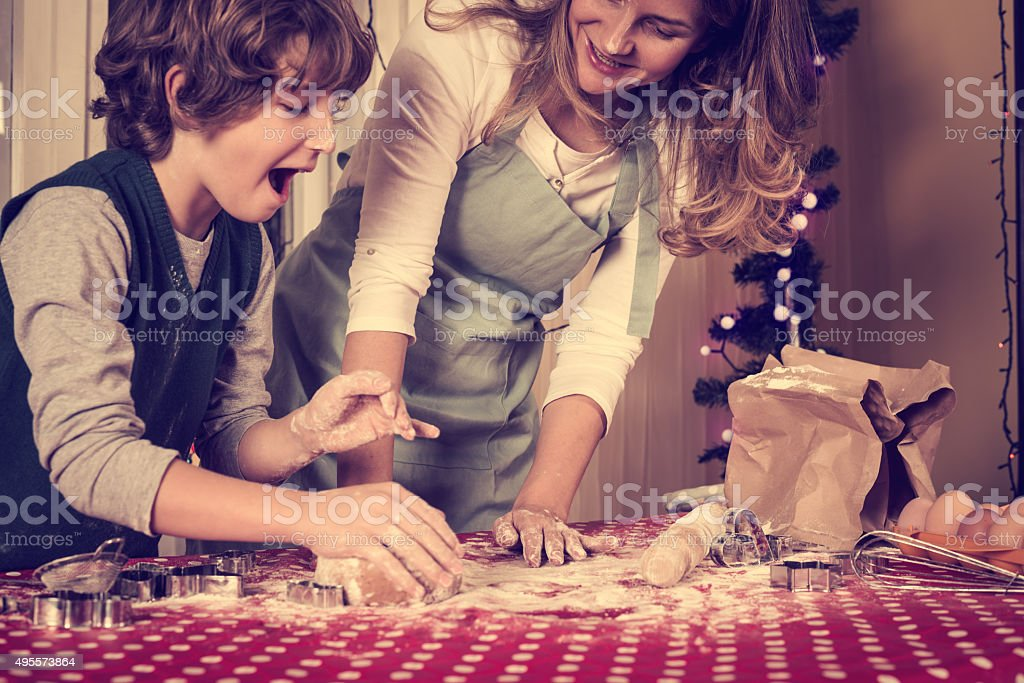 Child helping mother baking cookies for Christmas Eve stock photo
