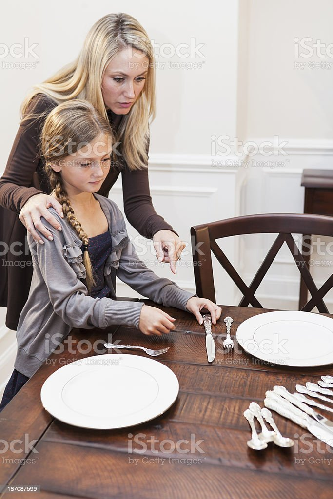 Child helping parent set the table for dinner stock photo