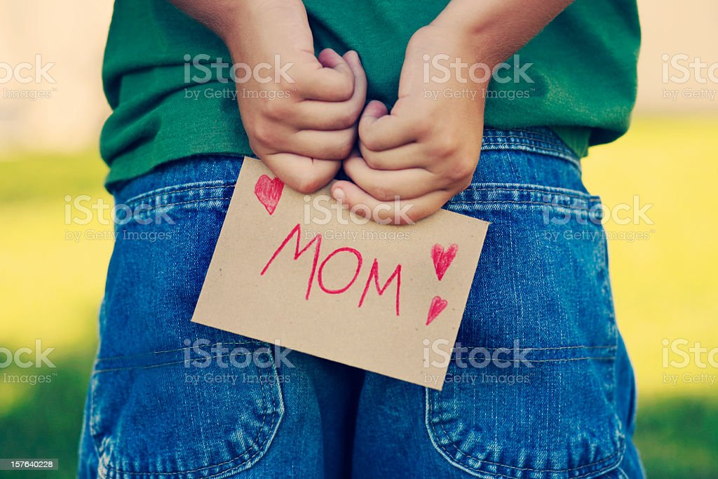 A child hiding a note for his mom behind his back stock photo