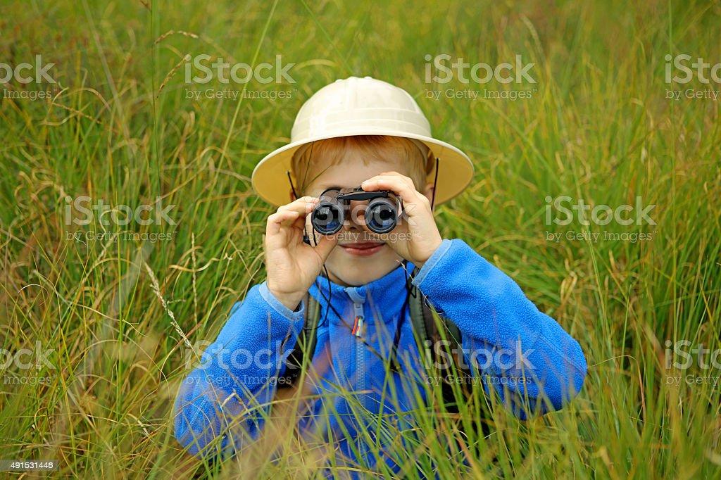 Child Hiding in High Grass Looking Through Binoculars stock photo