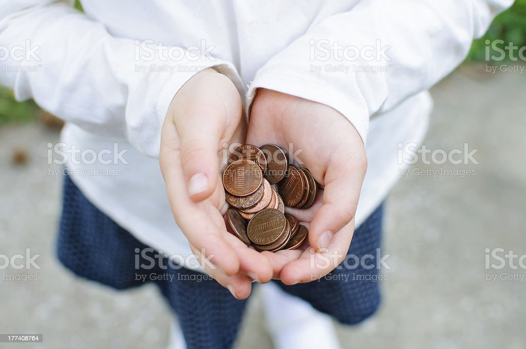 Child holding a handful of pennies stock photo