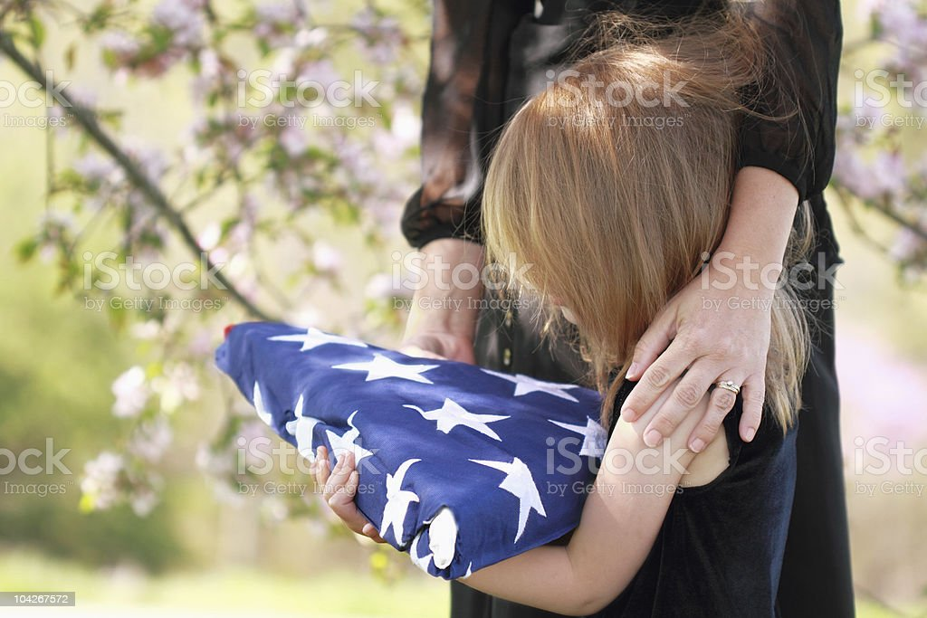 Child Holding a Parent's Folded American Flag stock photo