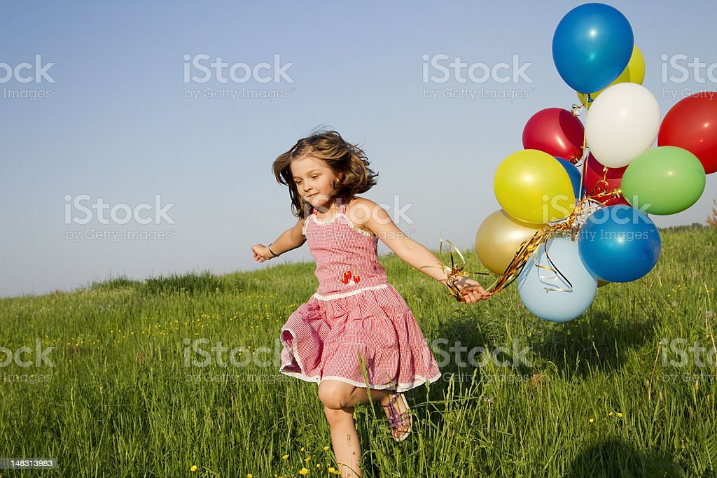 A child holding balloons and running through a field royalty-free stock photo
