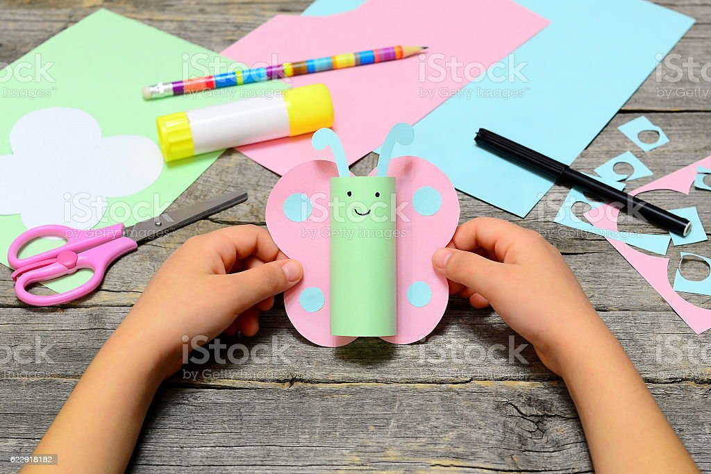 Child holding colored paper butterfly in hands stock photo