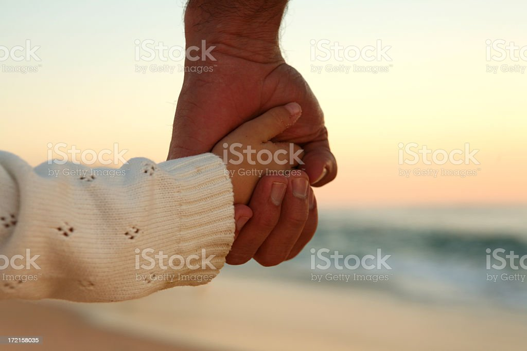 Child holding dads hand in the sunset royalty-free stock photo