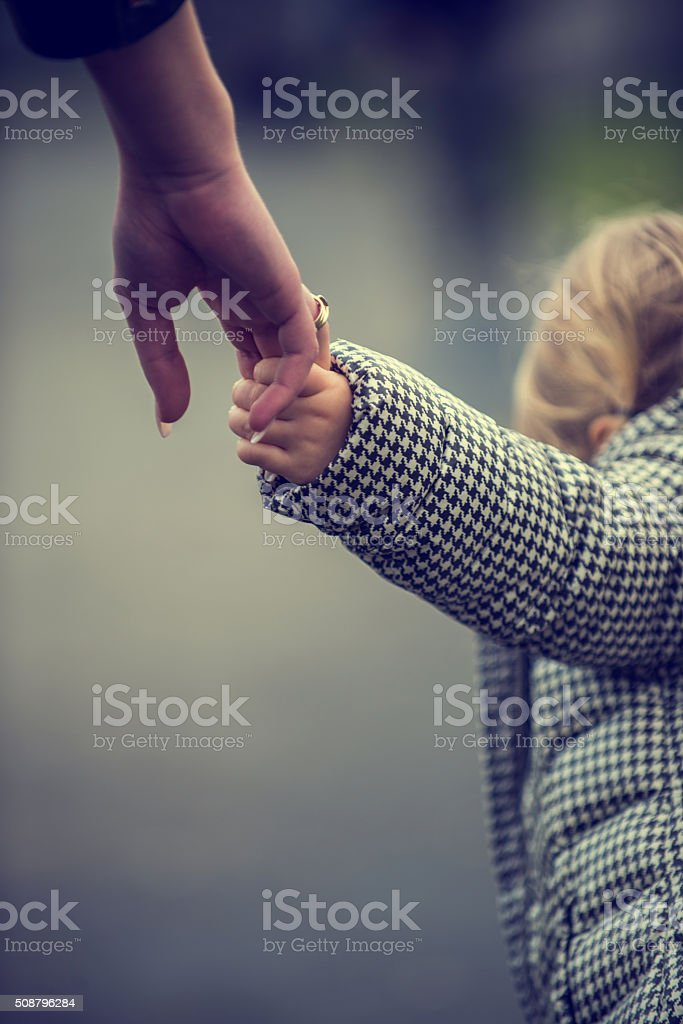 Child holding hand stock photo