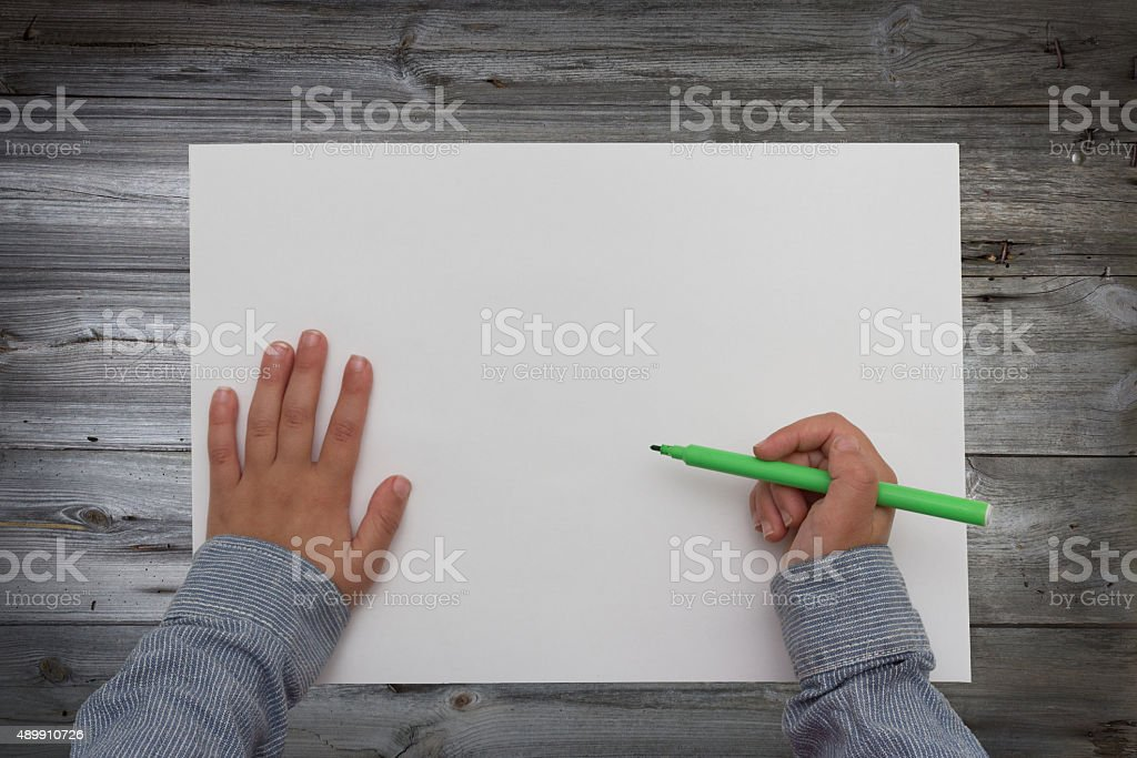 child holding pen over blank sheet of paper. kids hands stock photo