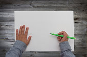 child holding pen over blank sheet of paper. kids hands