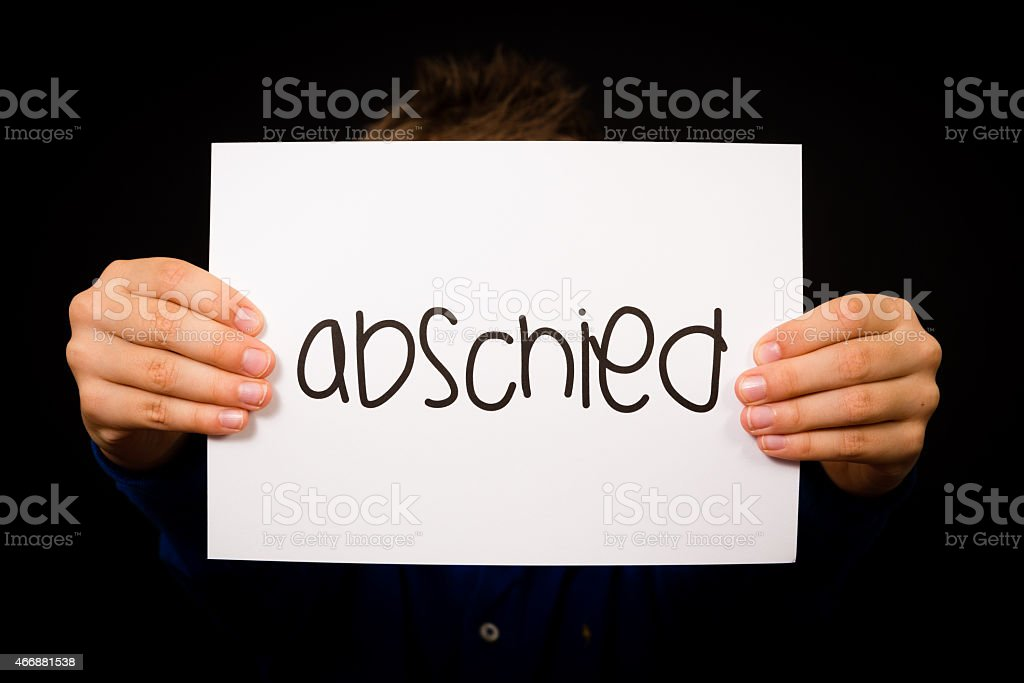 Child holding sign with German word Abschied - Goodbye stock photo
