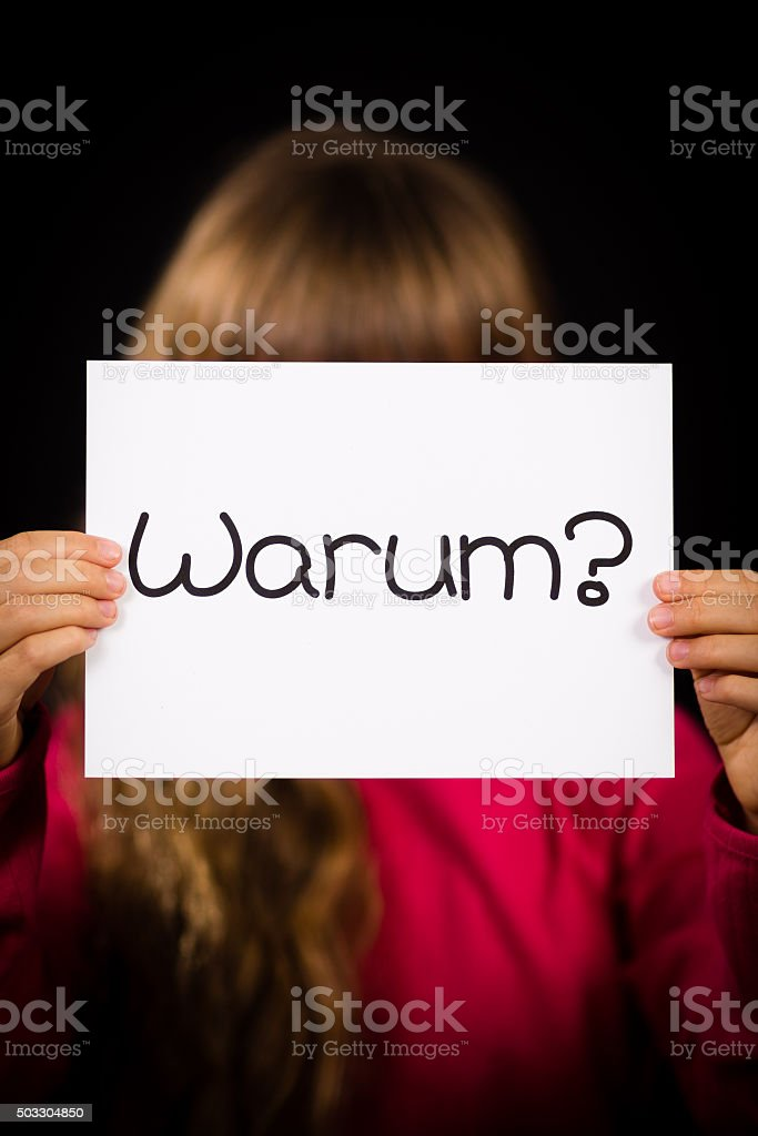 Child holding sign with German word Warum - Why stock photo