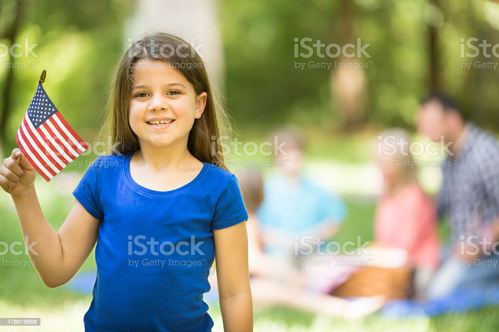 Child holds American flag outdoors, summer family picnic. July 4th. stock photo