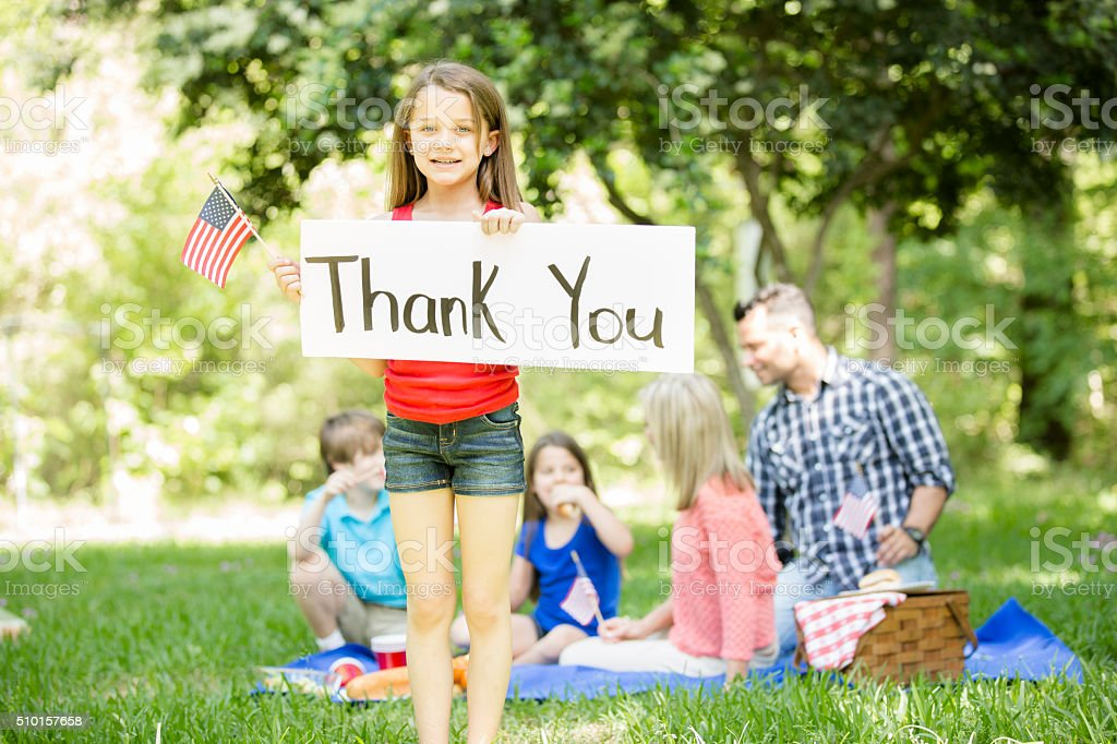 Child holds 'Thank You' sign with American flag. Memorial Day. stock photo