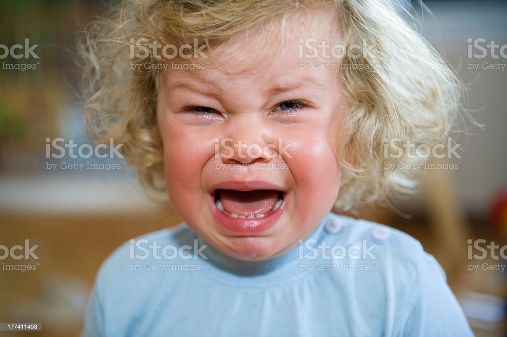 A child in a blue shirt that is crying royalty-free stock photo