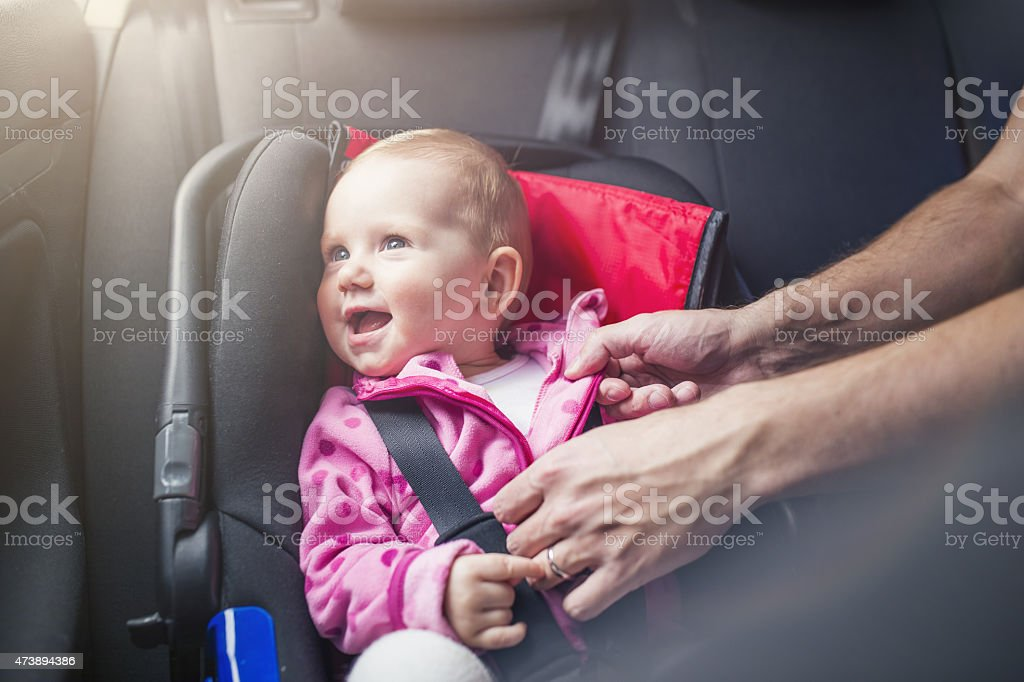 A child in a car buckled into a car seat stock photo