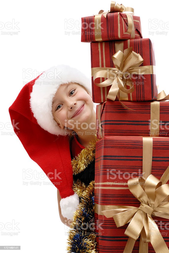A child in a Santa hat standing behind red presents royalty-free stock photo