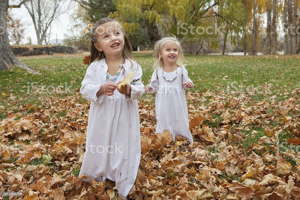 Child in Autumn Nature Setting with White Dress Playing royalty-free stock photo
