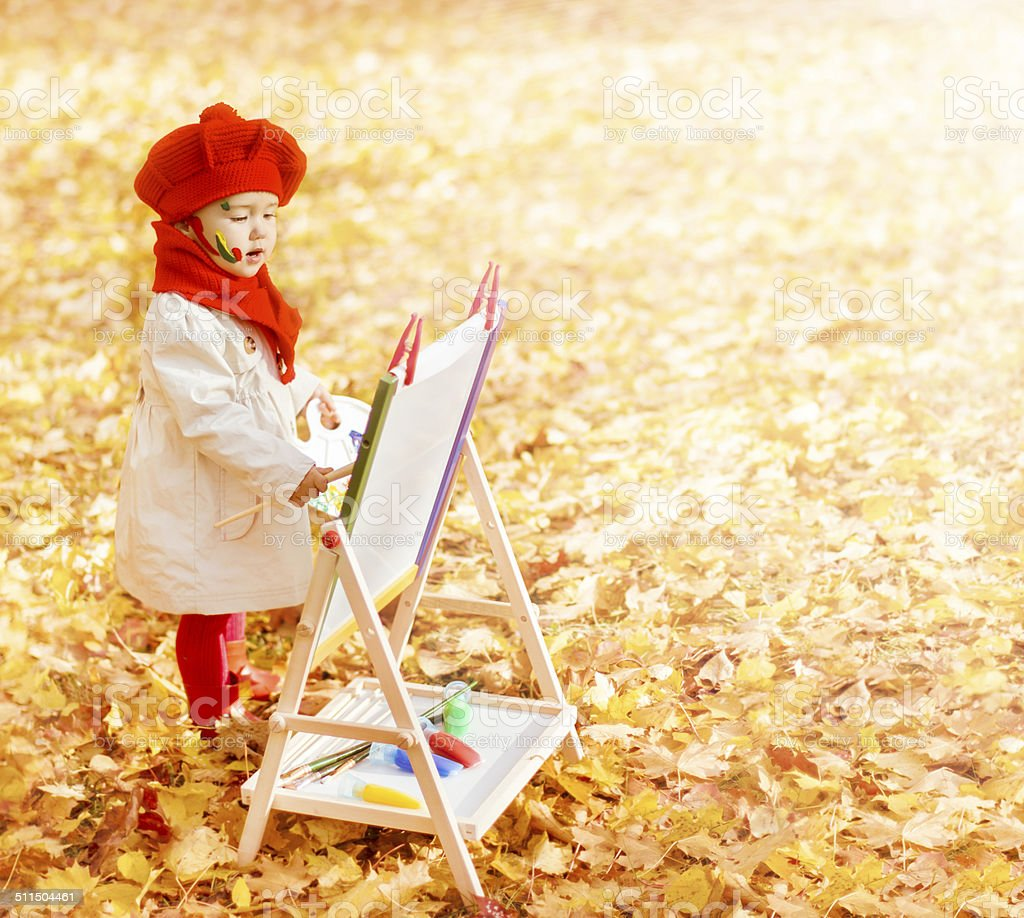 Child In Autumn Park Painting Picture On Easel, Fall Leaves stock photo