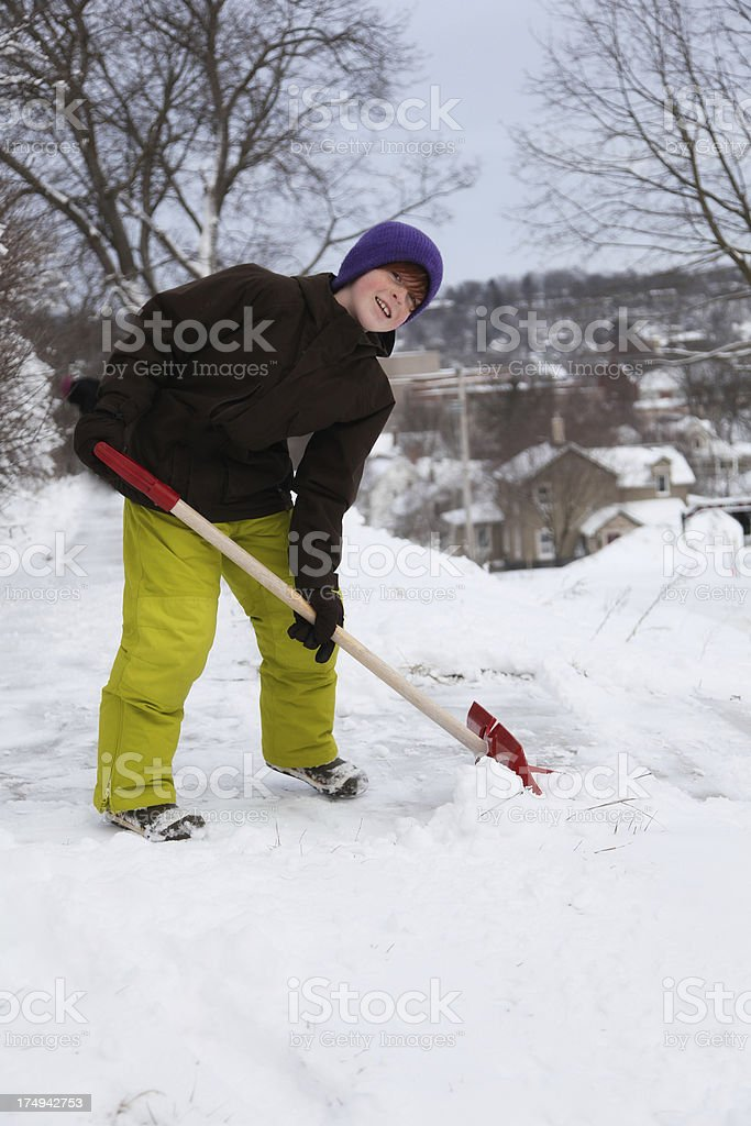 Child in Colorful Winter Wear Shoveling Snow royalty-free stock photo