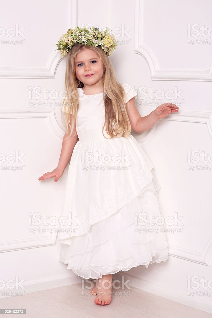 Child in dress with floral head wreath. White background stock photo