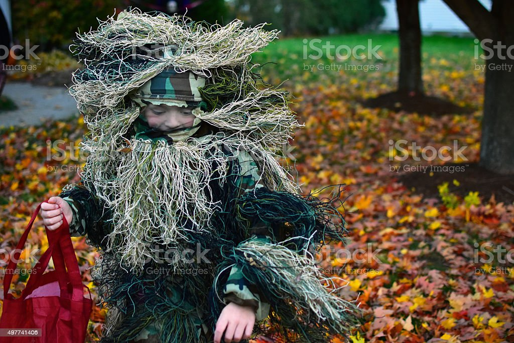 Child In Ghillie Suit Runs On Halloween stock photo