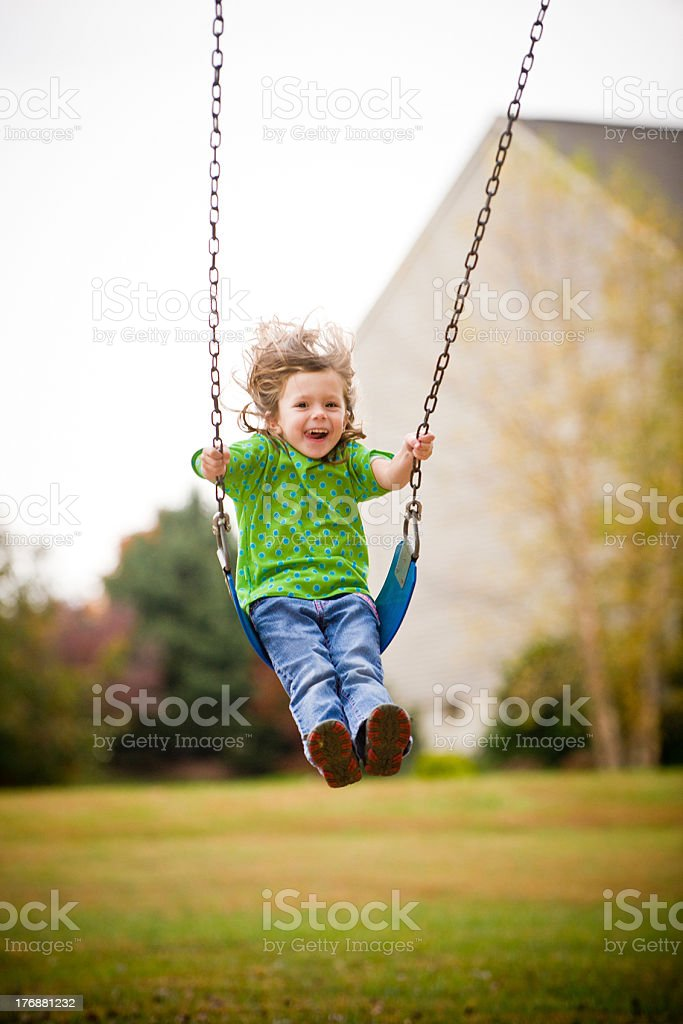 Child in green shirt on a swing royalty-free stock photo