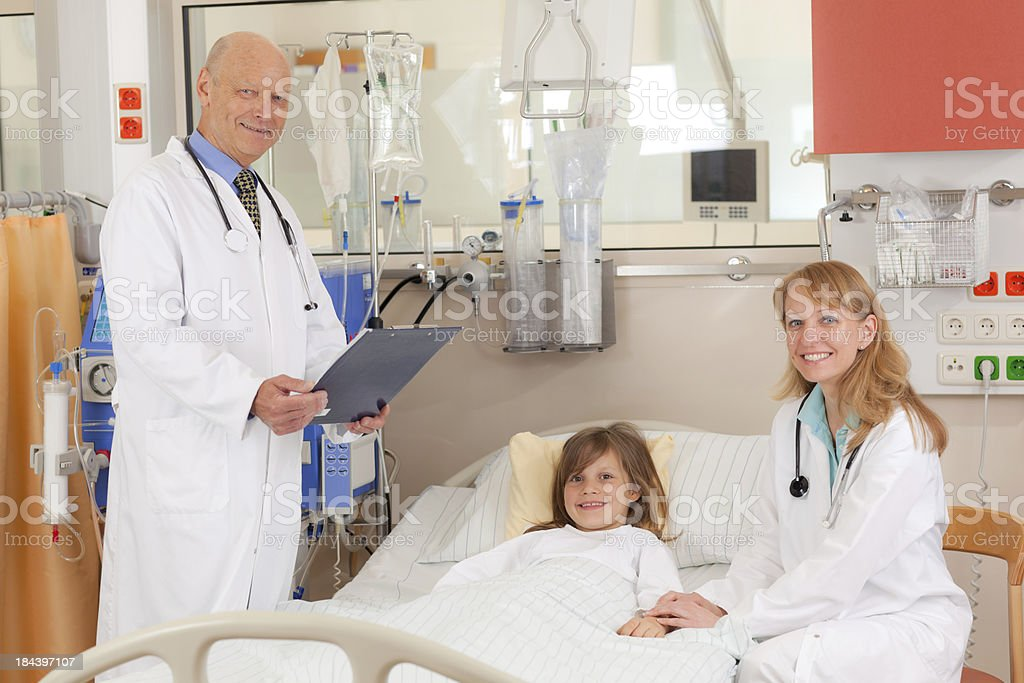 child in hospital with doctors stock photo