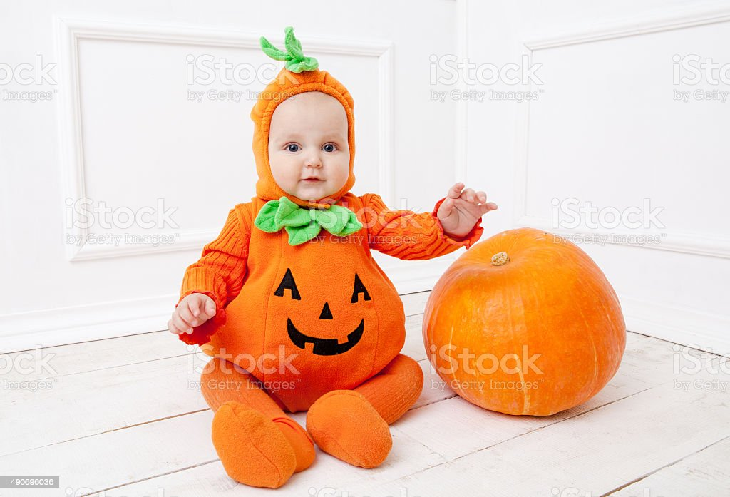 Child in pumpkin suit on white background with pumpkin stock photo