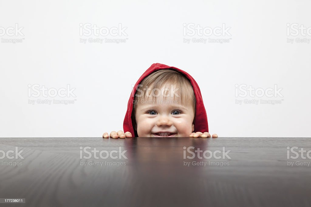 Child in red hood peering over a wood table on white stock photo