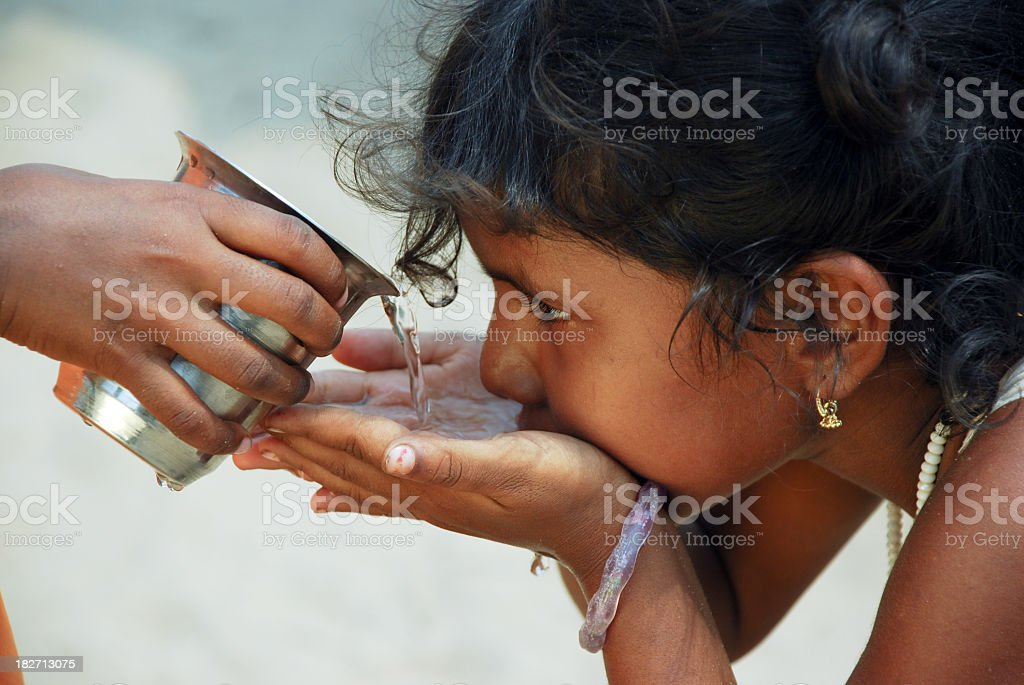 Child in solidarity act provides water to another stock photo