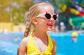 child in sunglasses near the pool at a water park