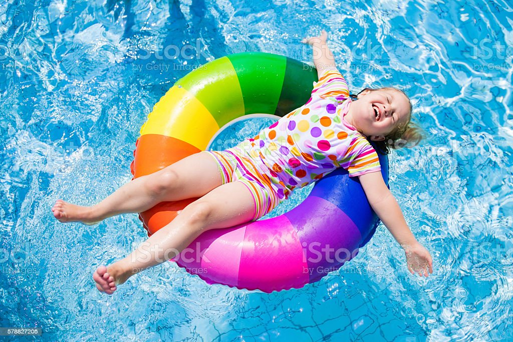 Child in swimming pool playing with colorful inflatable ring stock photo