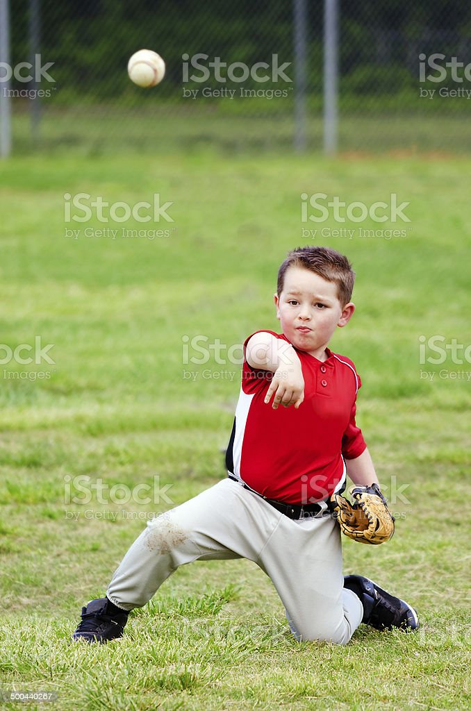 Child in uniform throwing baseball stock photo