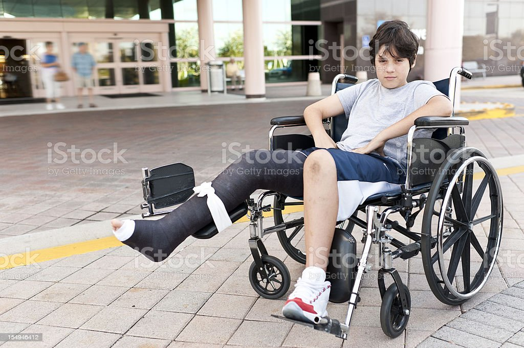 twelve years old child sitting in his wheel chair with his broken leg...