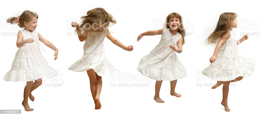 Child in white dress showing the movements of dance stock photo
