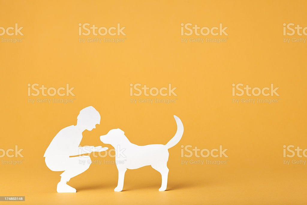 Child interacting with a dog: paper concept royalty-free stock photo