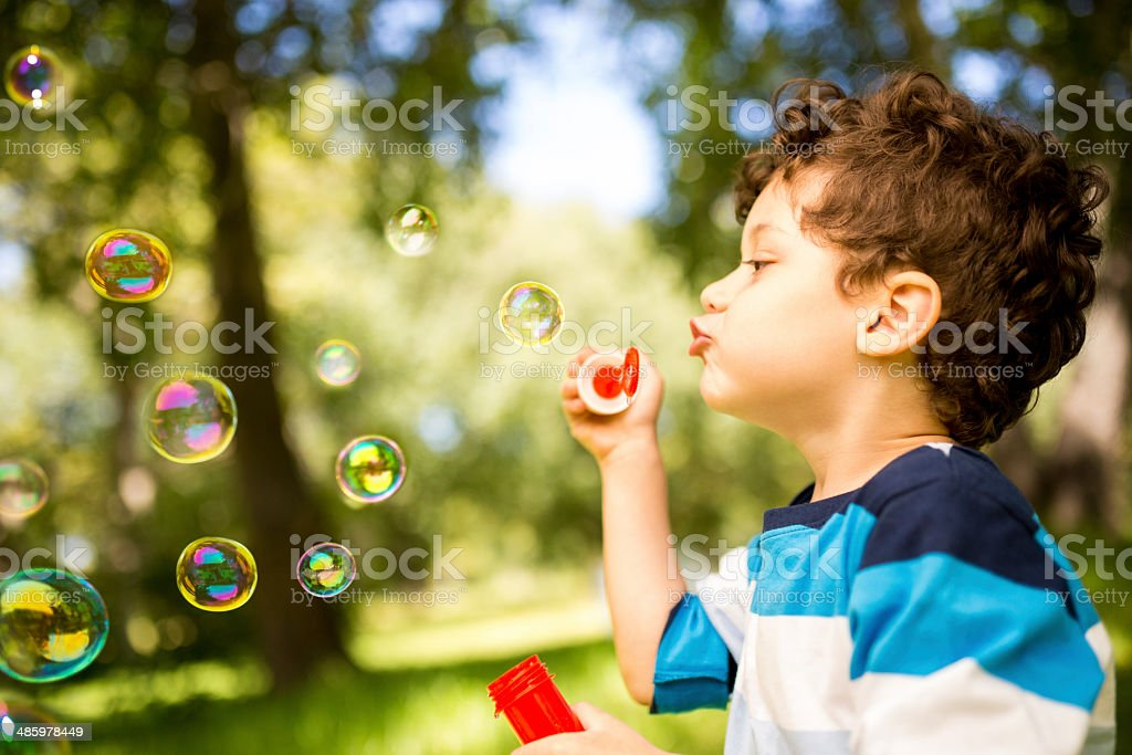 Child is blowing bubbles stock photo