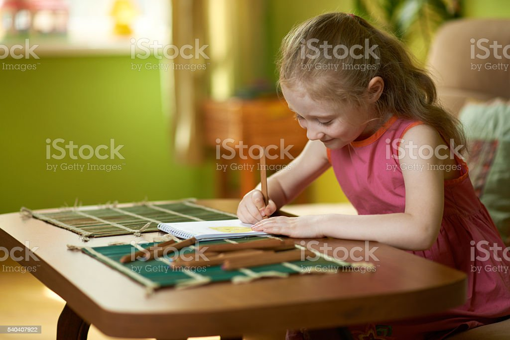 child is engaged in drawing pencil stock photo