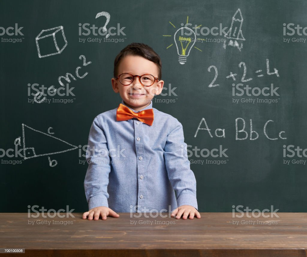 Child is in front of chalkboard