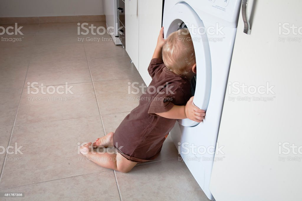 Child is looking into the washing machine stock photo