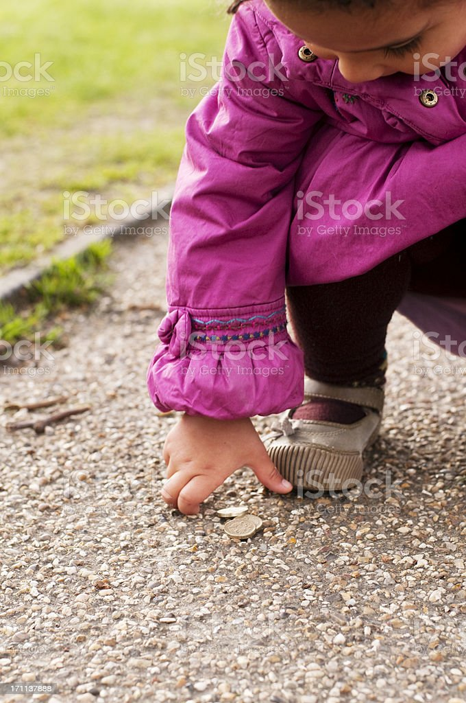Child is picking money from floor stock photo