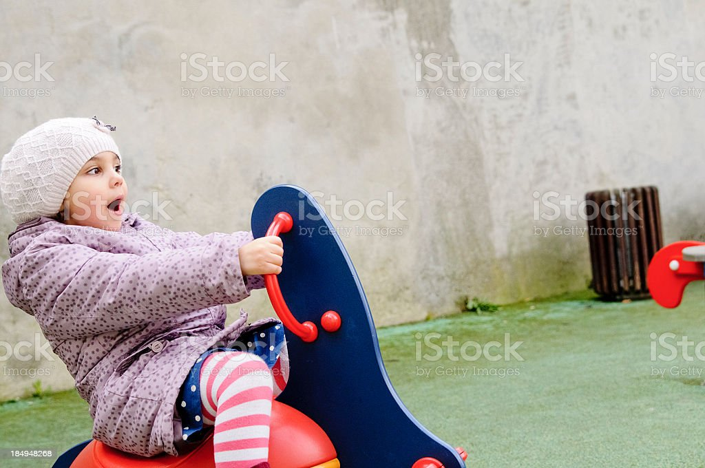 Child (5-6) Is Playing In Playground on Spring Ride stock photo