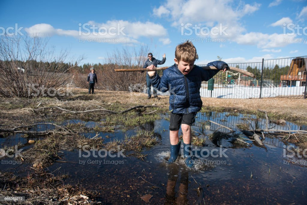 Child jumping into big puddle with angry dad watching stock photo