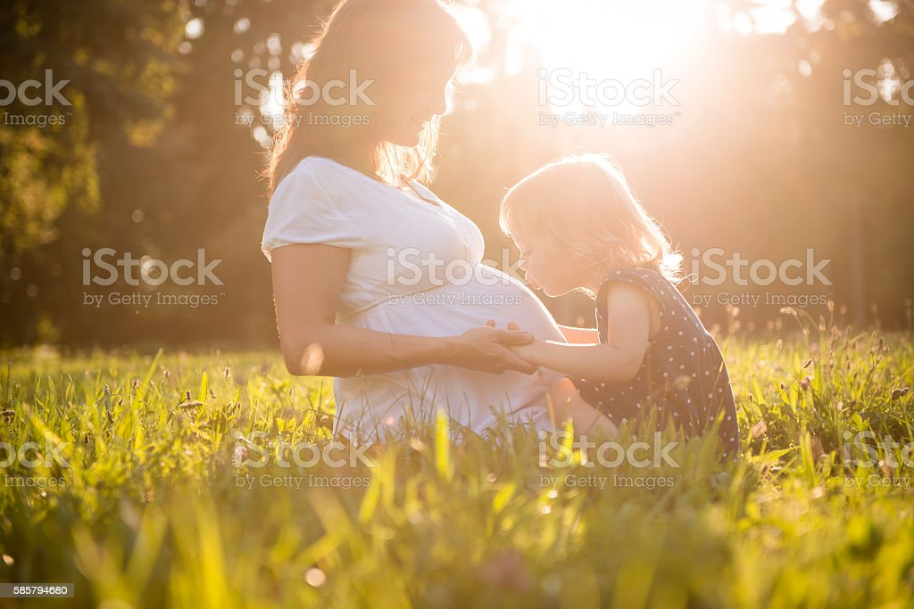 Child kissing belly og pregnant mother stock photo
