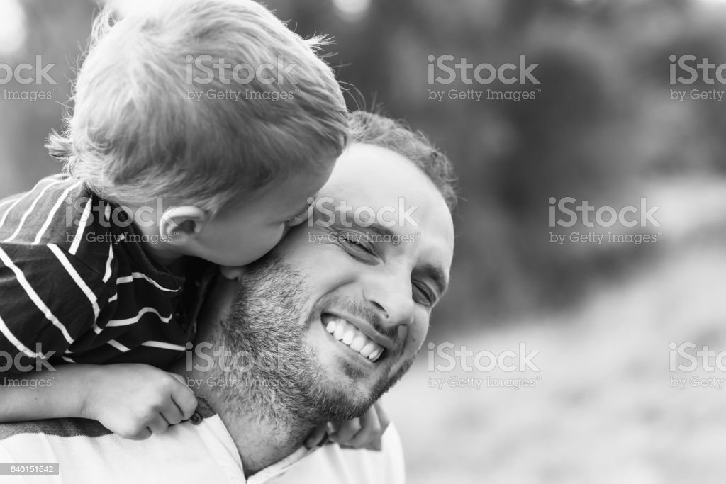 Child kissing father stock photo