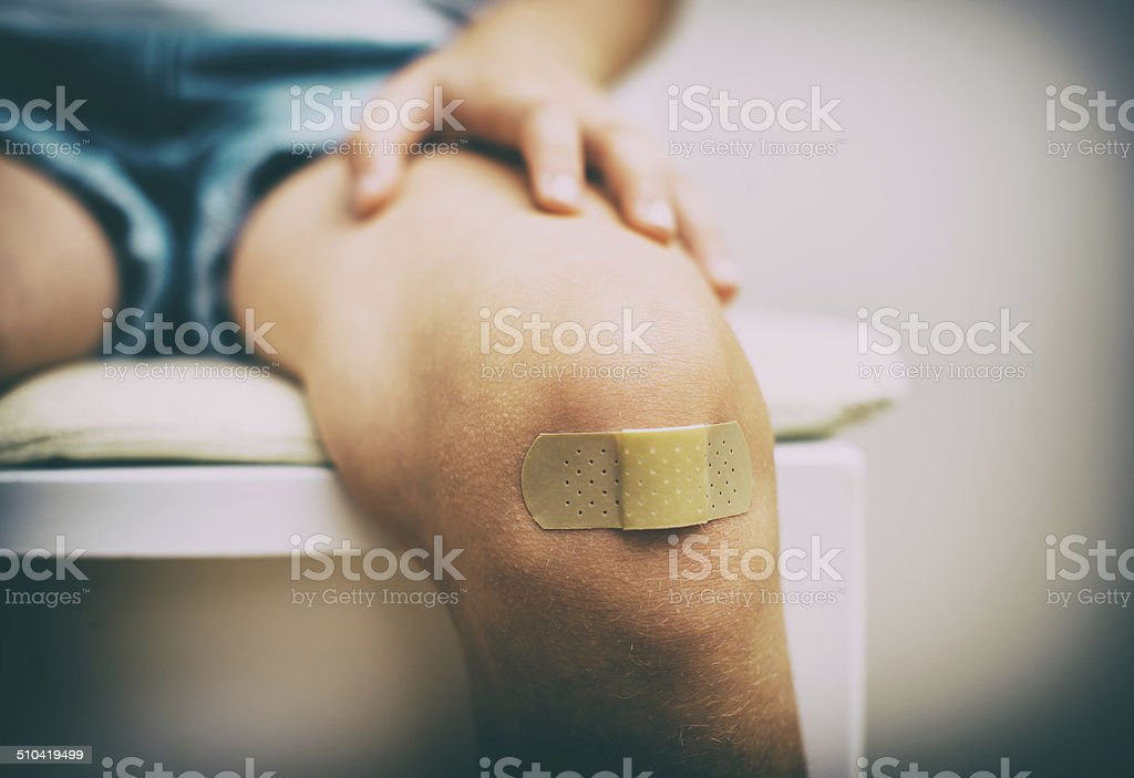 Child knee with an adhesive bandage. Vintage effect. stock photo