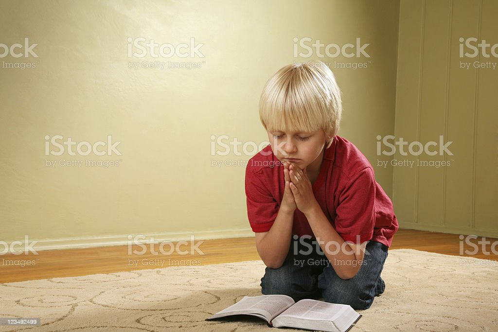 child kneeling and praying stock photo