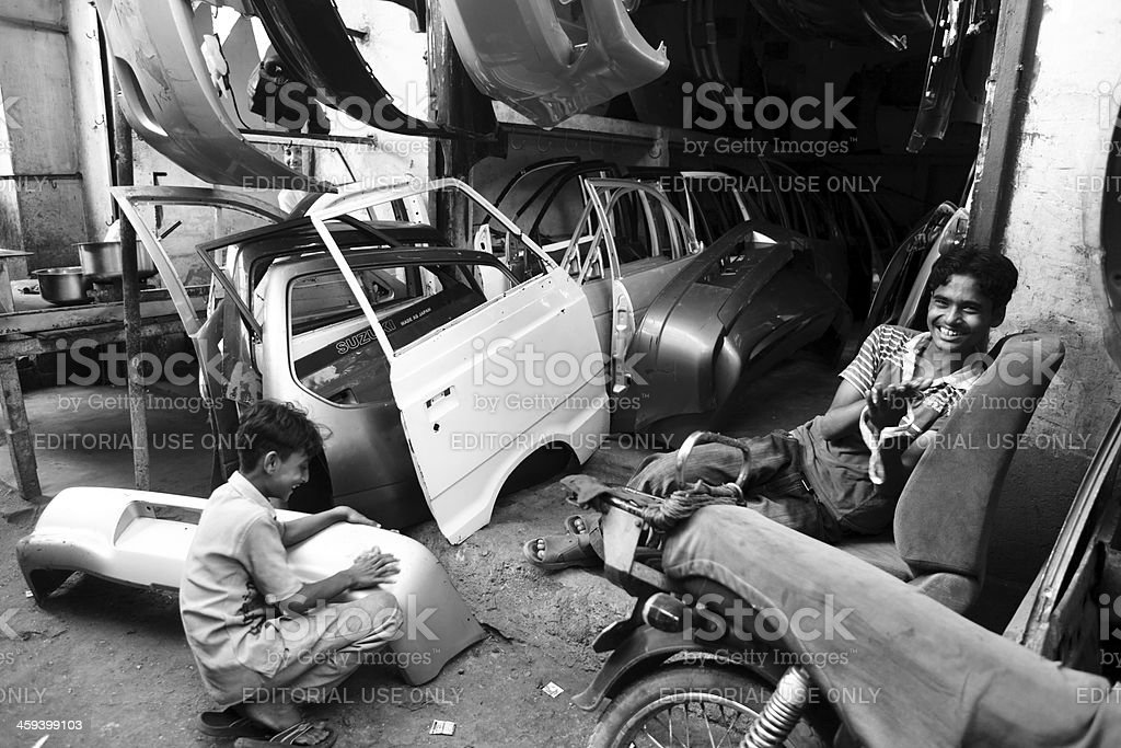 Child Labor at Body Shop Karachi Shershah Scrap Market royalty-free stock photo
