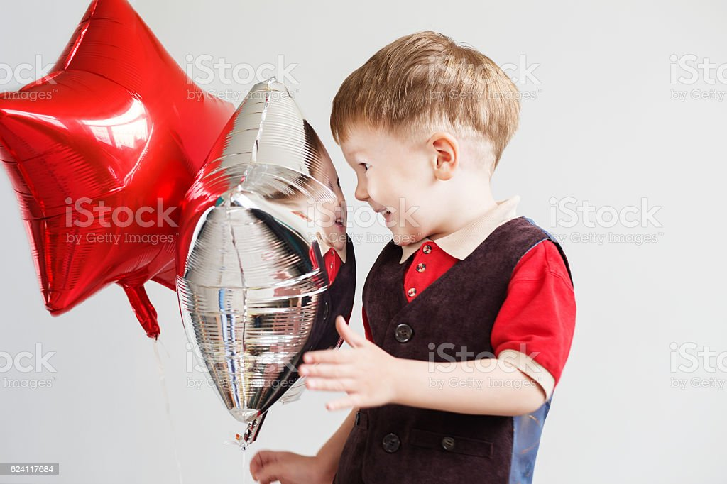 Child laughing looking at the reflection in a distorted mirror stock photo
