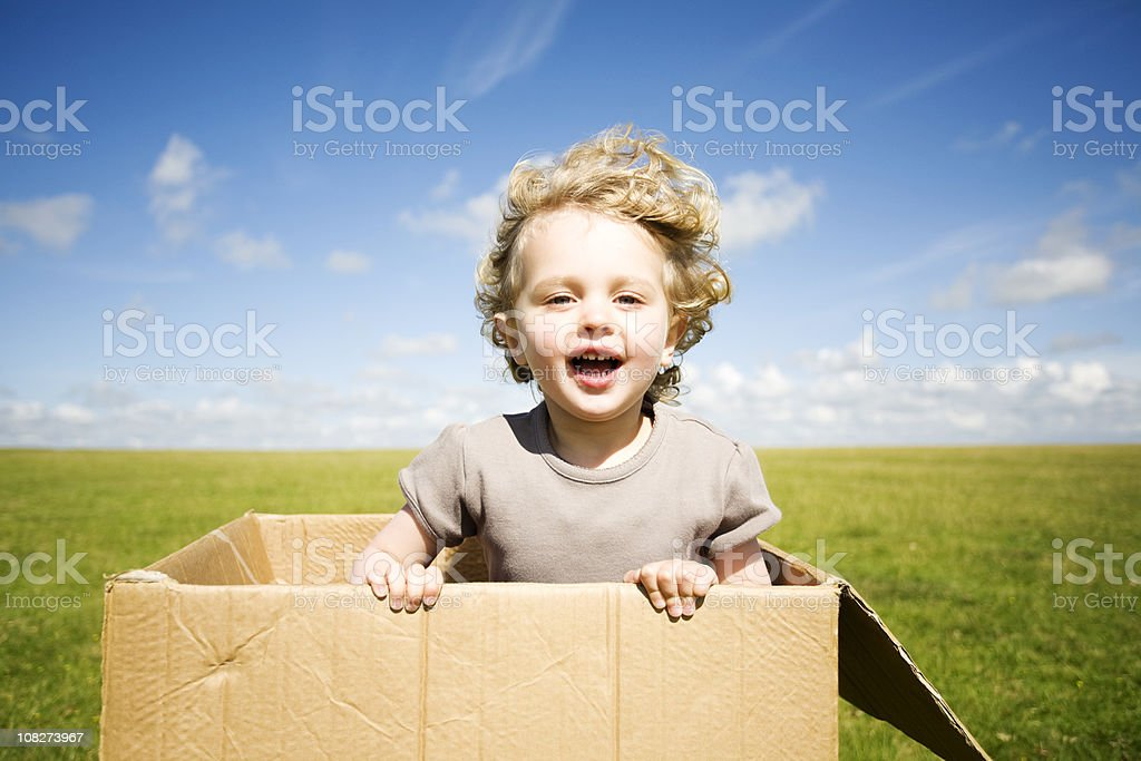 Child leaping out of a box stock photo