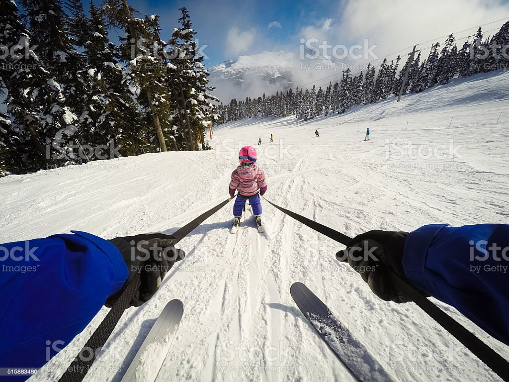 Child learning to ski with Dad stock photo